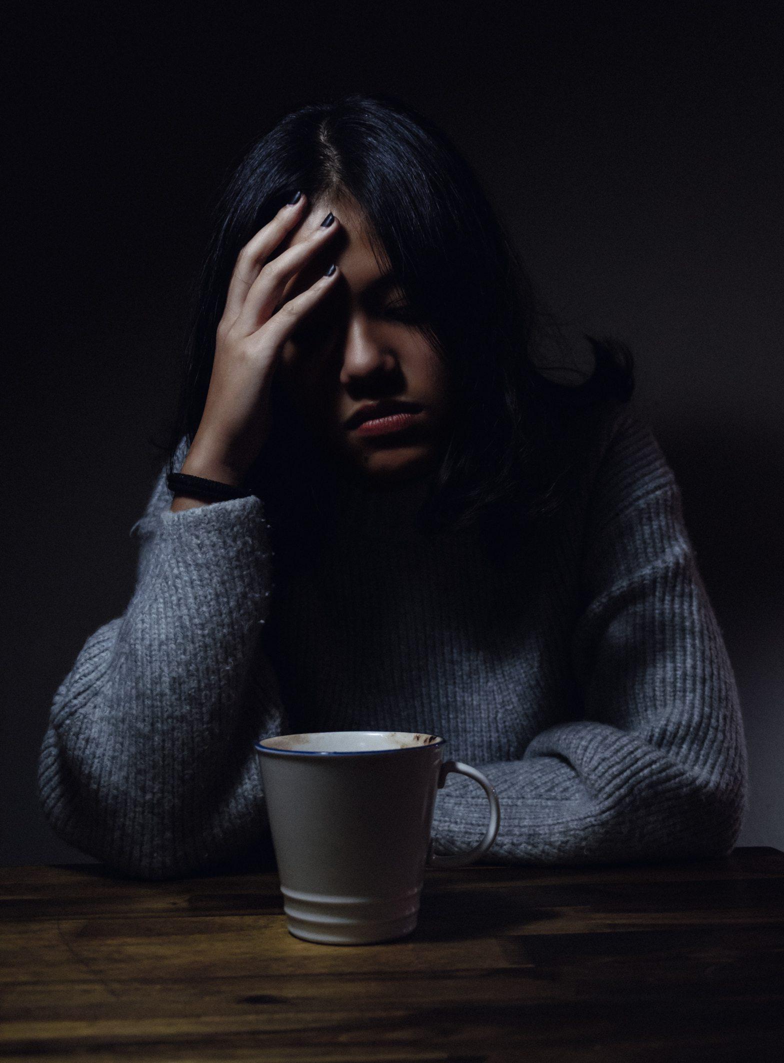A imagem mostra uma pessoa em sofrimento emocional com a cabeça curvada, aparência triste e com a mão direita segurando a cabeça. Uma caneca cinza está posicionado ao centro da imagem, sobre a mesa de madeira.